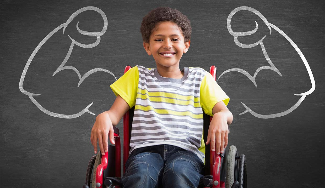 disabled South Carolina boy in wheel chair, in front of chalkboard with drawn-on muscle arms