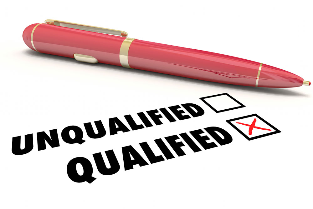 red pen laying next to words 'unqualified' and 'qualified', regarding medical status
