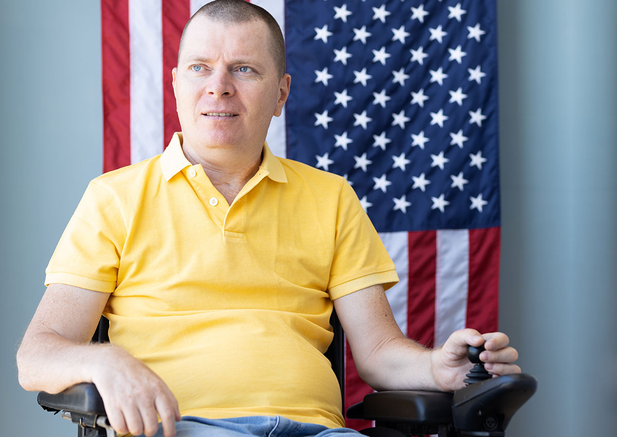 disabled veteran in wheelchair in front of American flag