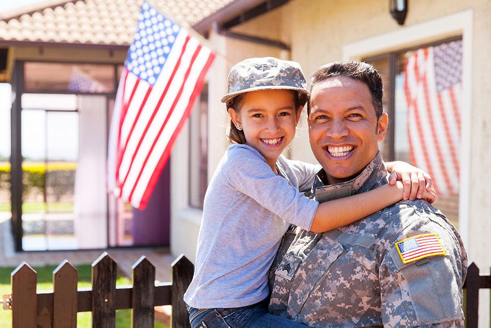 veteran in uniform holding small child