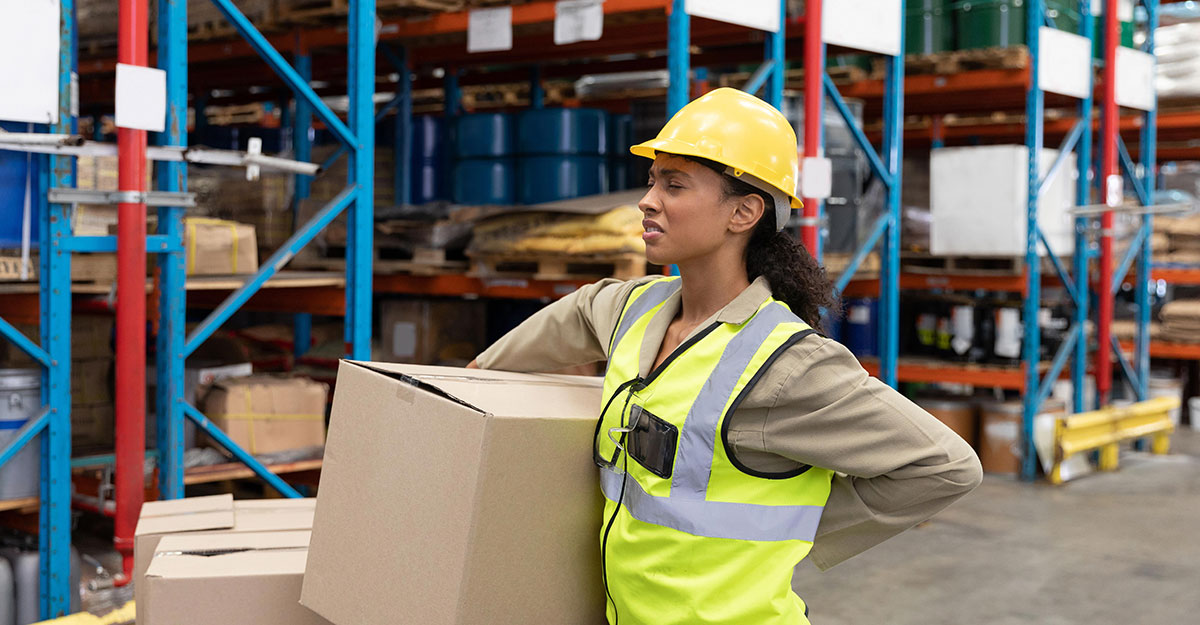 female warehouse worker experiencing back pain and wincing while holding her back